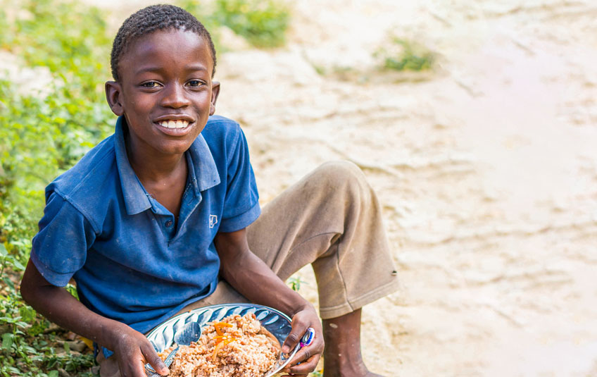 A boy sits on the ground holding a plate of food and smiling