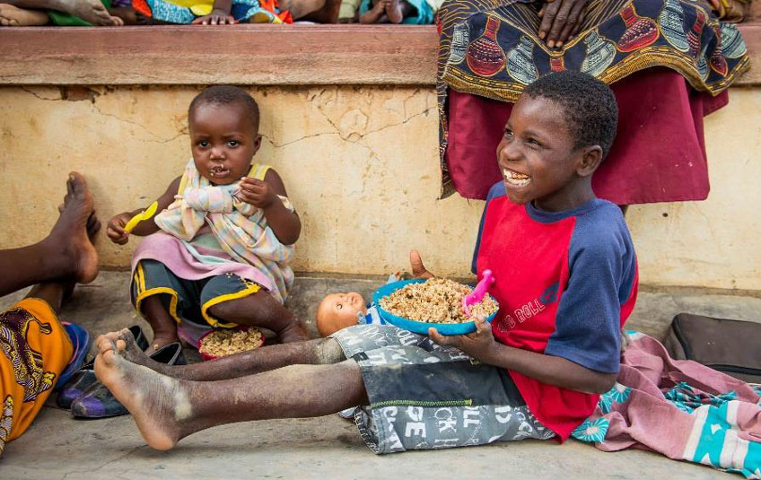 A Malawian boy sitting on the ground eating a bowl of FMSC food.