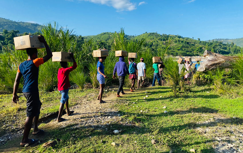 A group of Haitians carying FMSC food boxes on their heads
