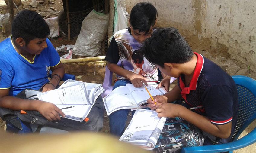 Three boys do homework together