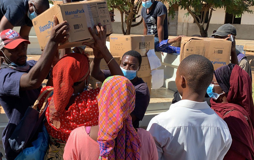 A woman in Mozambique receives a box of FMSC food from relief workers.