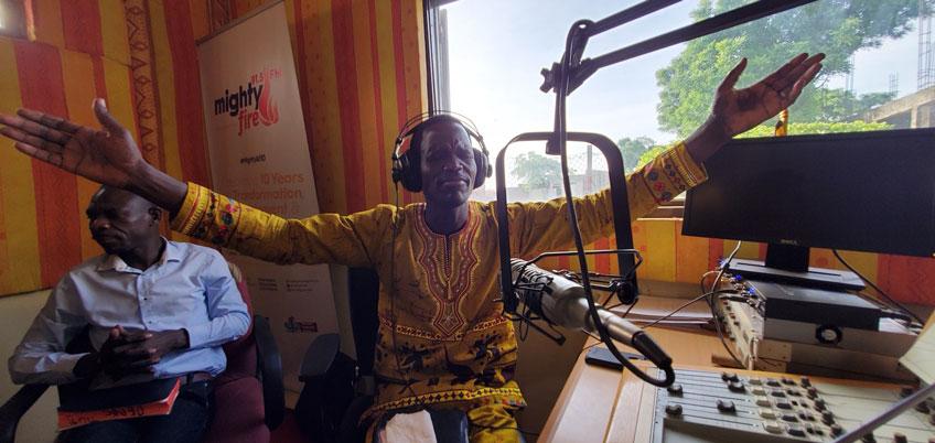 A Ugandan man lifts hands in prayer in a radio studio