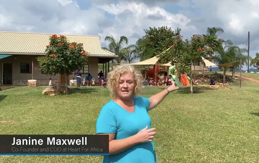 Janine Maxwell of Heart for Africa stands in the grass in front of a building in Eswatini