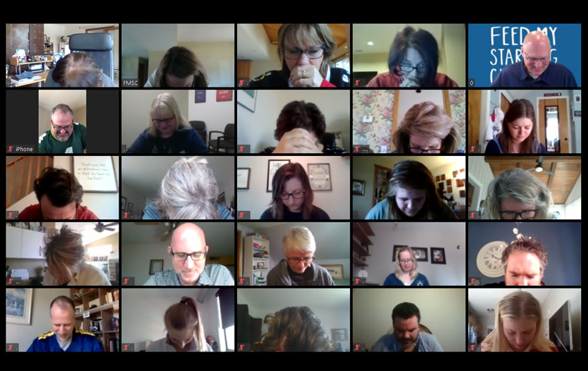 Screenshot with tiled images of FMSC employees praying over a Zoom video conference