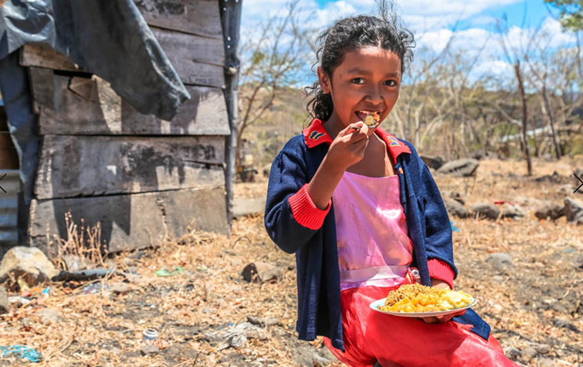 A girl eating a bowl of food