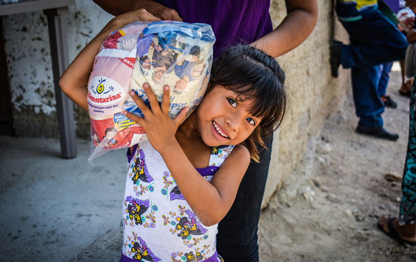 a girl holding a bag with an FMSC MannaPack meal bag inside it