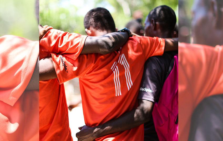 three Haitian men in soccer jerseys