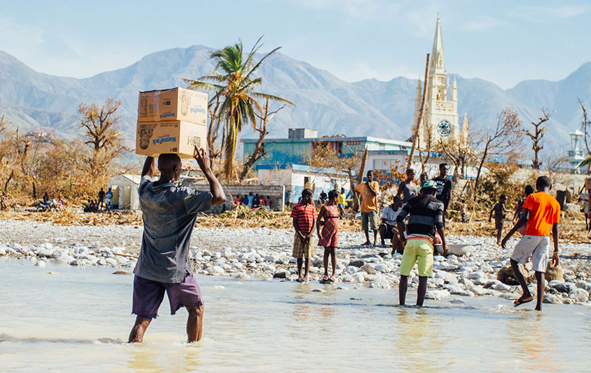a group carrying MannaPack boxes across a creek in Haiti