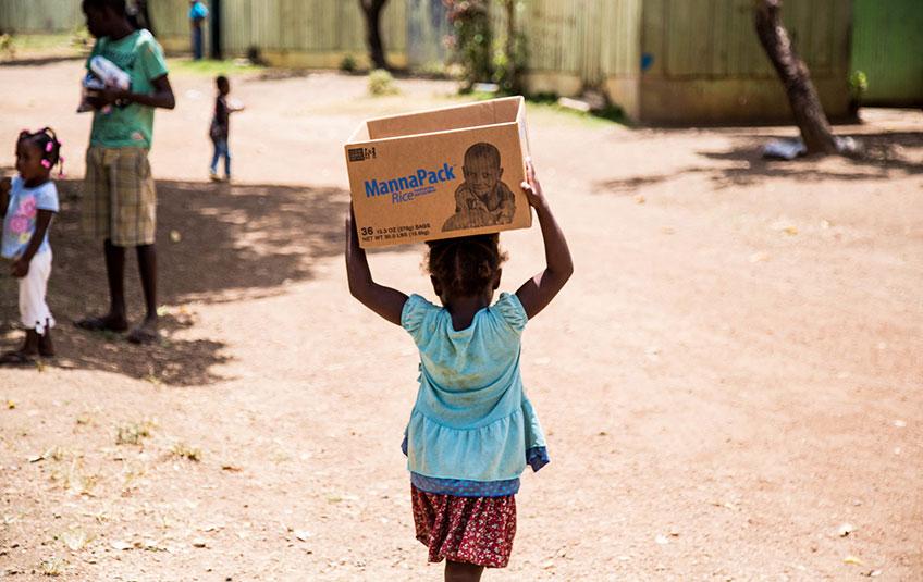 A girl carries an FMSC MannaPack box