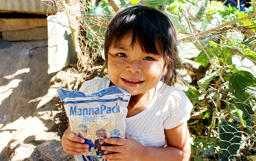 A girl holds a back of FMSC MannaPack Rice