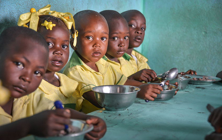 5 children sit at a table eating FMSC food