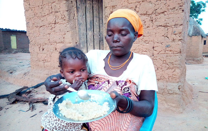 a mother feeds her daughter FMSC'S MannaPack meals
