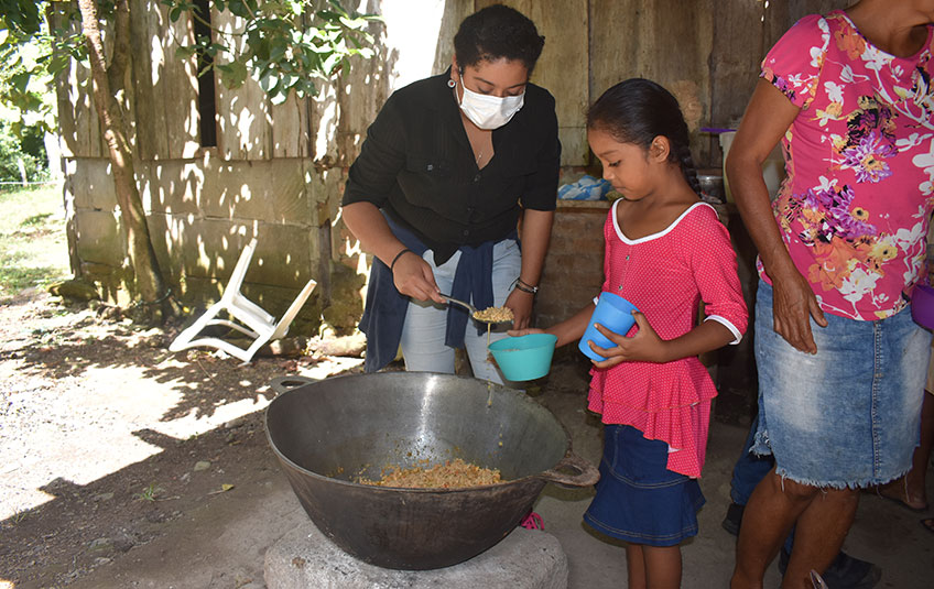 a girl receiving a bowl of FMSC's MannaPack meals