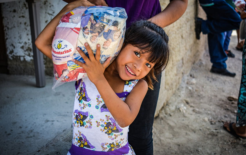 A girl holds a bag containing FMSC's MannaPack meals