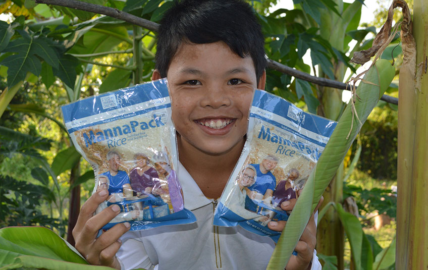A boy holding two bags of MannaPack meals beside his face