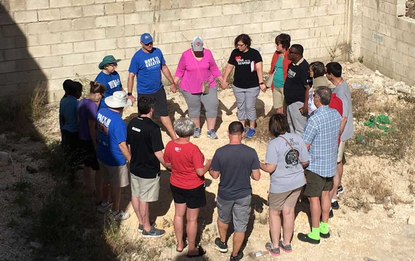 A group of FMSC staff and volunteers praying