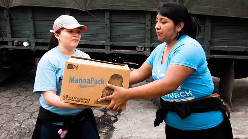 A woman passes a box of FMSC food to another woman