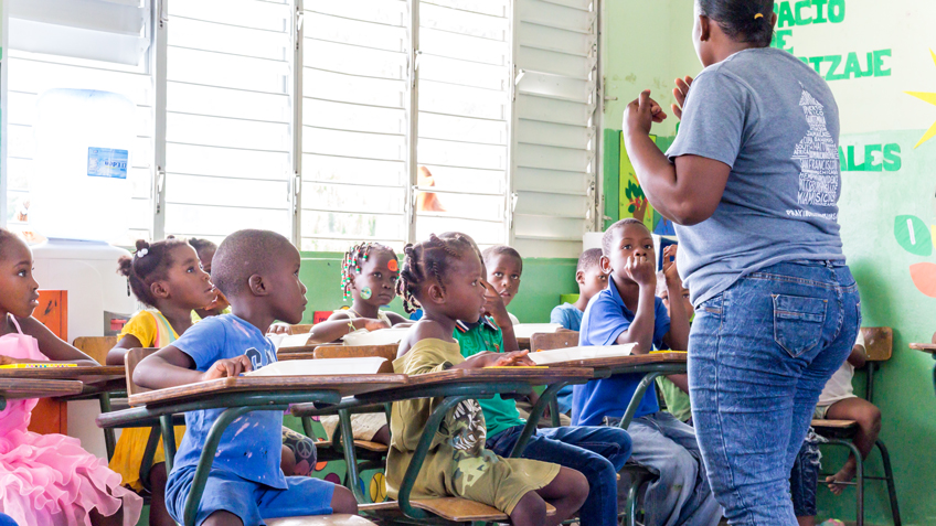 A woman teaches a classroom of kids in the Dominican Republic as part FMSC's feeding programs