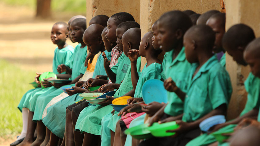 Ugandan school children eating FMSC meals as part of a school feeding program