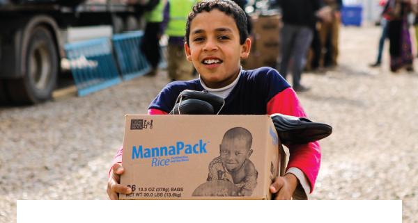 child holding MannaPack box full of food