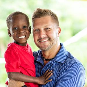 Haiti Bible Mission CEO Mark Stockeland holding a child