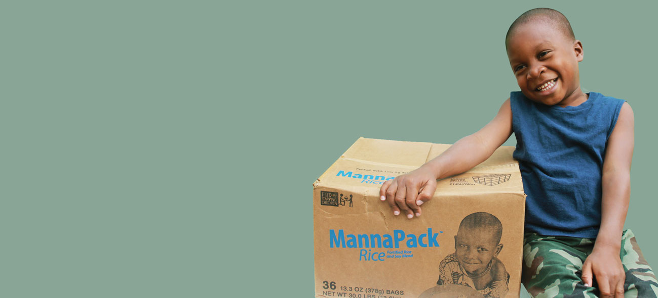 a boy holding a box of FMSC MannaPack food over a green background