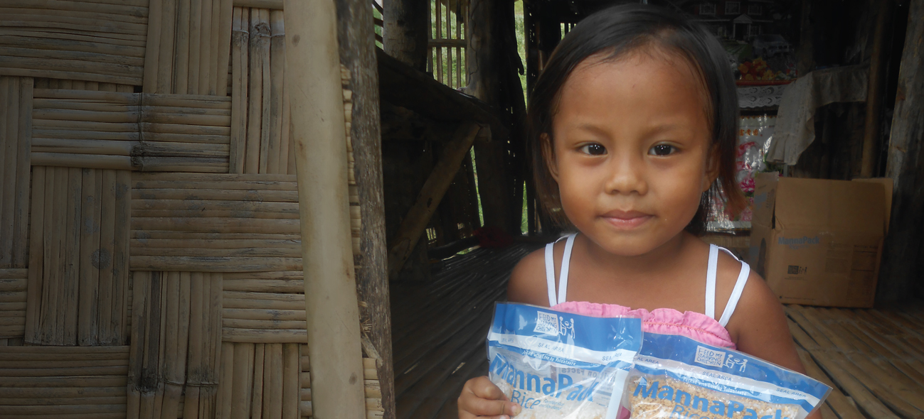 A Filipino girl holds two bags of FMSC food beside her bamboo house