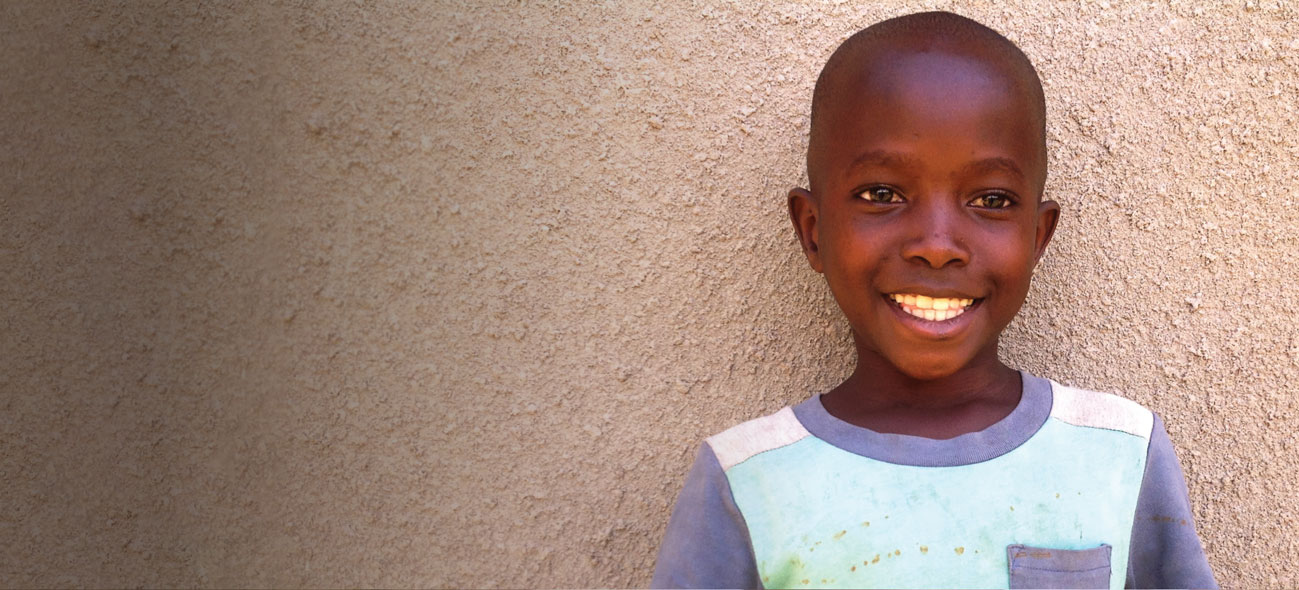 A smiling Ugandan boy stands in front of a beige wall