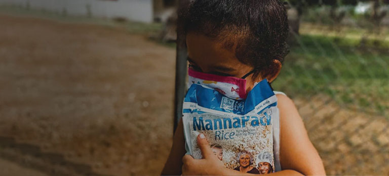a masked Venezuelan girl clutches a bag of FMSC food