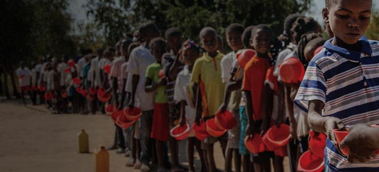 Children standing in a line awaiting FMSC food
