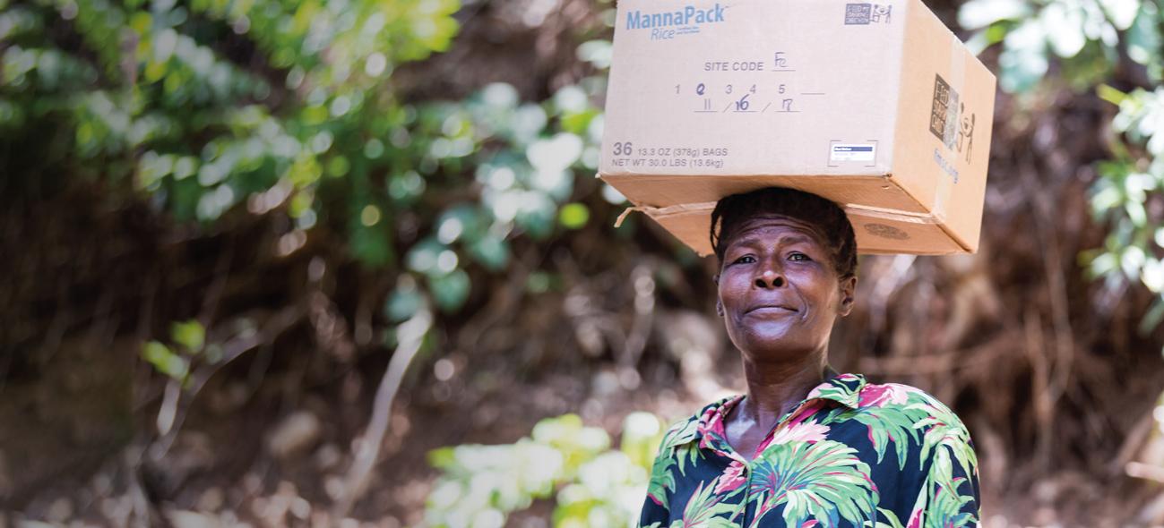 Haitian woman holding a box of FMSC food
