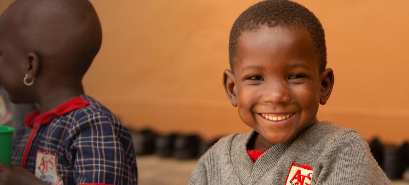 Lauza, a Ugandan girl, smiles at the camera