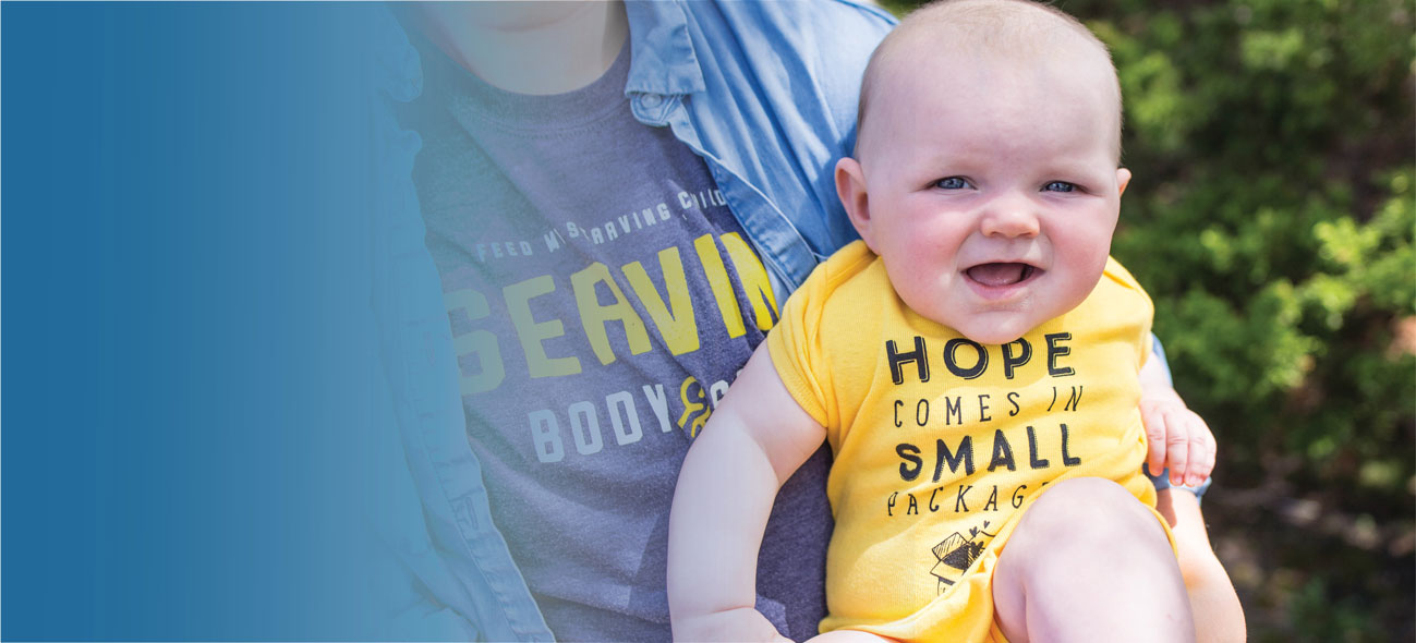 "a mother holding a baby wearing an FMSC branded onesie that says ""Hope comes in small packages"""