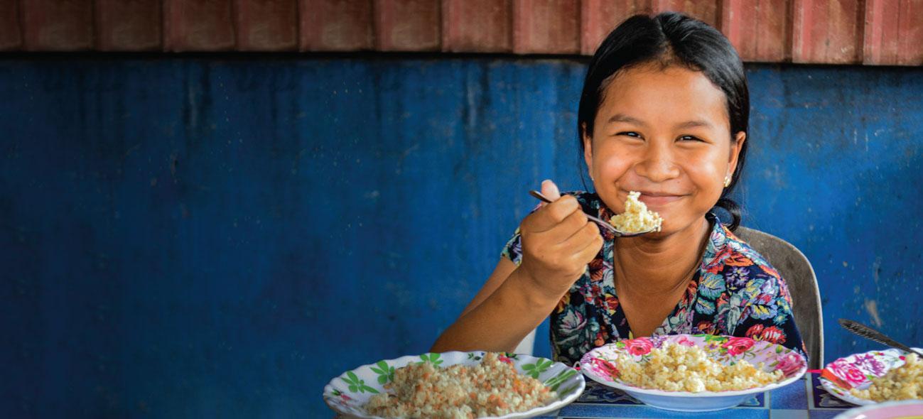 A girl eating FSMC food.