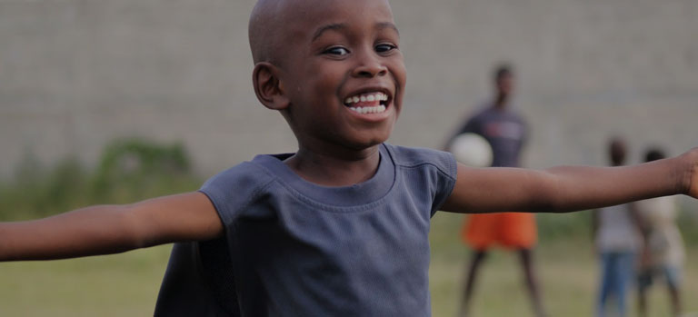 A smiling boy running with outstretched arms