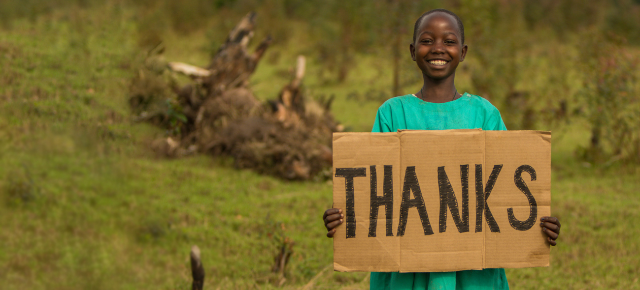 "Ugandan child holding a ""Thanks"" sign"