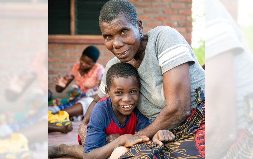 A Malawian boy sitting on his grandmother's lap, both smiling